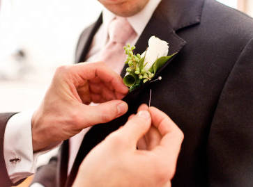 Pinning on Grooms Lapel Badge for wedding ceremony